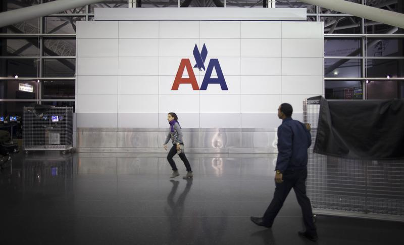 People walk past an American Airlines logo at John F. Kennedy (JFK) airport in in New York