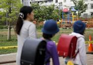 School children and a woman walk past the park where high radiation has been detected near a playground equipment (rear R) in Toshima ward, Tokyo April 24, 2015. REUTERS/Toru Hanai