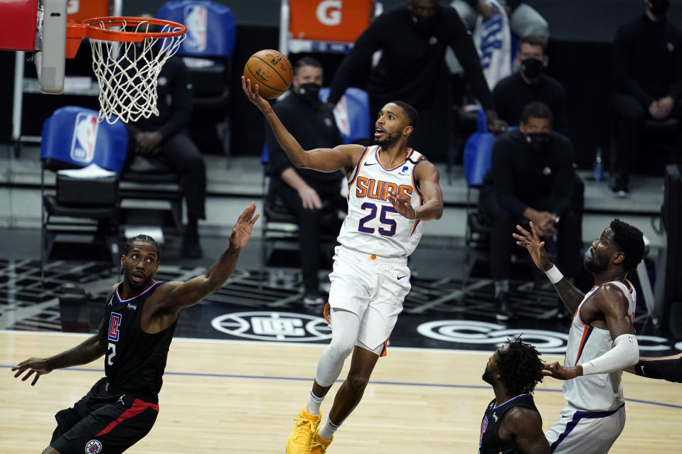 Phoenix Suns forward Mikal Bridges (25) scores over Los Angeles Clippers forward Kawhi Leonard, left, during the first half of an NBA basketball game Thursday, April 8, 2021, in Los Angeles. (AP Photo/Marcio Jose Sanchez)