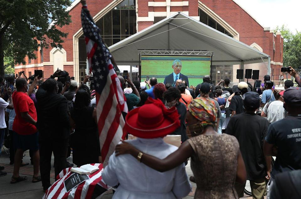 <p>Mourners watched the funeral from an overflow area outside the church. One woman held and American flag while watching President Obama give his eulogy. </p>