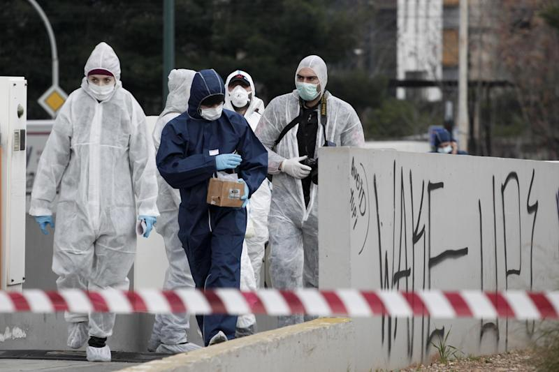 Greek Police forensic experts search for evidence after an unknown attacker fired an automatic rifle at the building on the capital's busy Syngrou Avenue, Athens, on Monday, Jan. 14, 2013. A gunman fired a spray of bullets at the headquarters of the governing center-right New Democracy party near central Athens early Monday, with one hitting an office occasionally used by the prime minister, officials said. No one was hurt. (AP Photo/Petros Giannakouris)