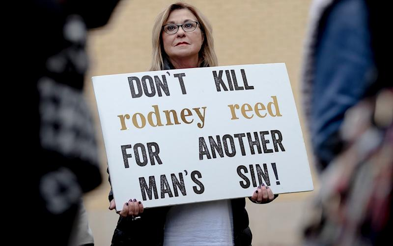 A woman holds a sign during a protest against the execution of Rodney Reed on Wednesday, Nov. 13, 2019, in Bastrop, Texas. Protesters rallied in support of Rodney Reed's campaign to stop his scheduled Nov. 20 execution which was given a temporary stay on Nov 15 - Austin American-Statesman