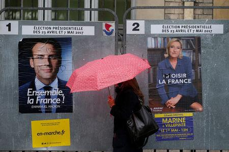 A woman walks past the new official posters of candidates for the 2017 French presidential election Emmanuel Macron, head of the political movement En Marche !, or Onwards !,  and Marine Le Pen, French National Front (FN) political party leader, in Paris