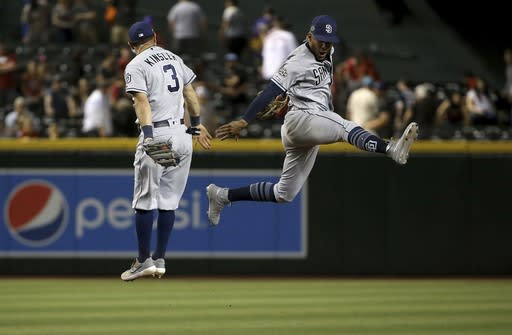 San Diego Padres shortstop Fernando Tatis Jr., right, celebrates a win against the Arizona Diamondbacks with second baseman Ian Kinsler (3) after a baseball game Saturday, April 13, 2019, in Phoenix. The Padres won 5-4. (AP Photo/Ross D. Franklin)