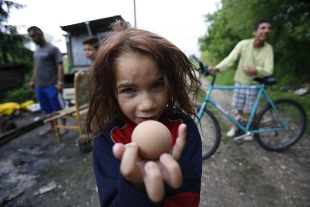 <p>Roma girl Samira Ramic poses for photo as she shows a boiled egg, during St. George's Day celebration with her family members, in the village of Kiseljak, near Tuzla,140 kms north of Sarajevo, May 6, 2017. Members of the Roma minority community in Bosnia and Herzegovina celebrated their biggest holiday, St. George's Day, or Djurdjevdan, with traditional rituals such as taking baths and washing hands with water from church wells and cracking eggs, as the holiday marks the advent of spring. (Photo: Amel Emric/AP) </p>