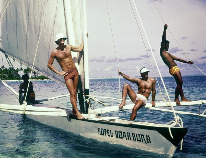 "<span class=""caption"">The ideal male body didn't always include chiseled abs.</span> <span class=""attribution""><a class=""link rapid-noclick-resp"" href=""https://www.gettyimages.com/detail/news-photo/summer-1975-three-models-pose-on-a-hotel-bora-bora-sailing-news-photo/1171950396?adppopup=true"" rel=""nofollow noopener"" target=""_blank"" data-ylk=""slk:Chris von Wangenheim/Conde Nast via Getty Images"">Chris von Wangenheim/Conde Nast via Getty Images</a></span>"