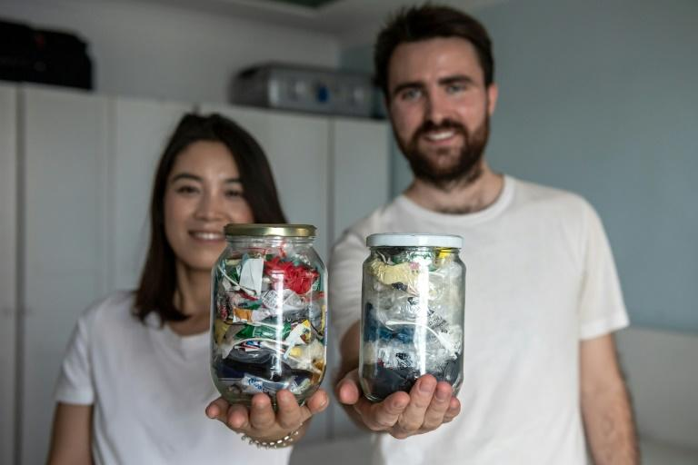 Carrie Yu and Joe Harvey, founders of zero-waste shop The Bulk House, pose with jars containing all of their personal waste collected over three months at their home in Beijing (AFP Photo/NICOLAS ASFOURI)