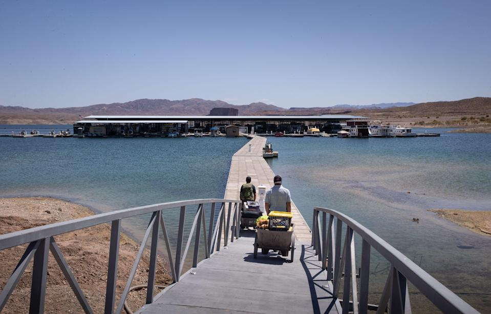 Barbaros Demircar (right) and Mike Darin haul gear down to their boat at Temple Bar Marina on May 10, 2021, in the Lake Mead National Recreation Area, Arizona.