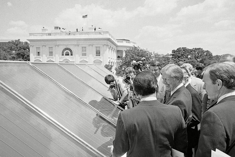 President Jimmy Carter (right) surrounded by reporters as he inspects solar panels installed at the White House during his presidency. | Harvey Georges/AP/Shutterstock
