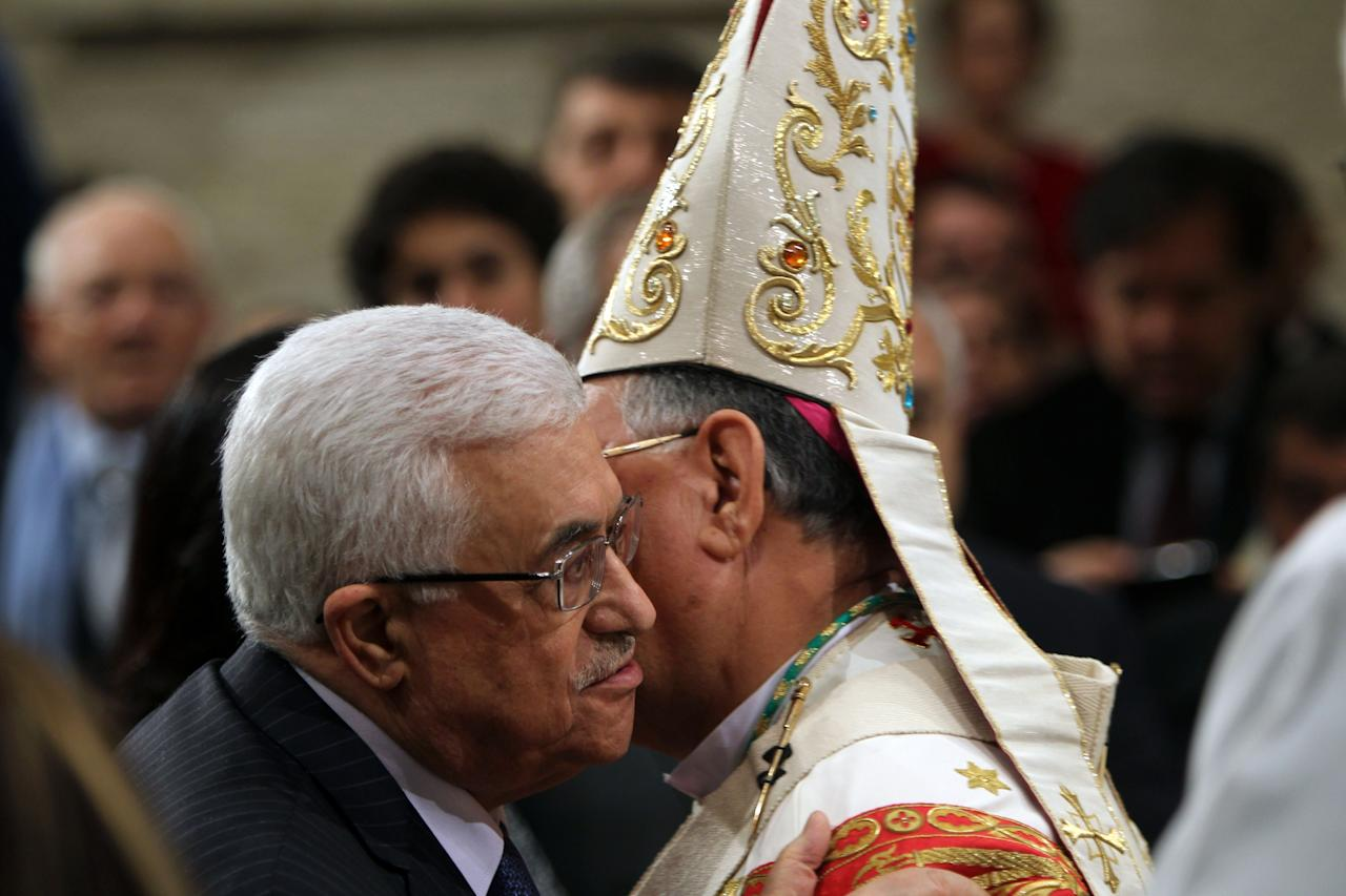 BETHLEHEM, WEST BANK - DECEMBER 25: Foud Twal, the Latin Patriarch of the Holy Land, embraces Palestinian President Mahmoud Abbas (L) as the Palestinian Authority leader attends the Christmas Midnight Mass in Saint Catherine's Church on December 25, 2012 in Bethlehem, West Bank. Thousands of pilgrims made their way to the Church of the Nativity this week to worship at the sacred site believed to be the birthplace of Jesus. (Photo by Abed Al Hashlamoun-Pool/Getty Images)