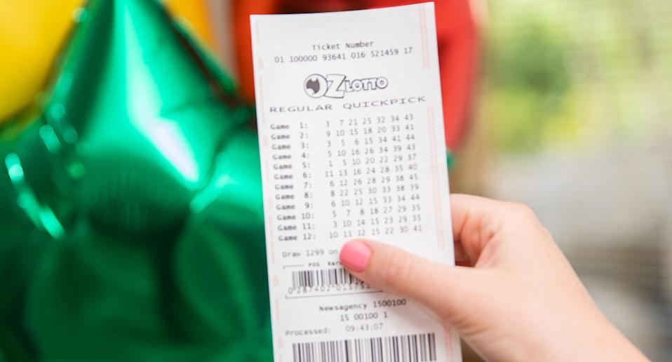 Photo shows person holding an Oz Lotto ticket.