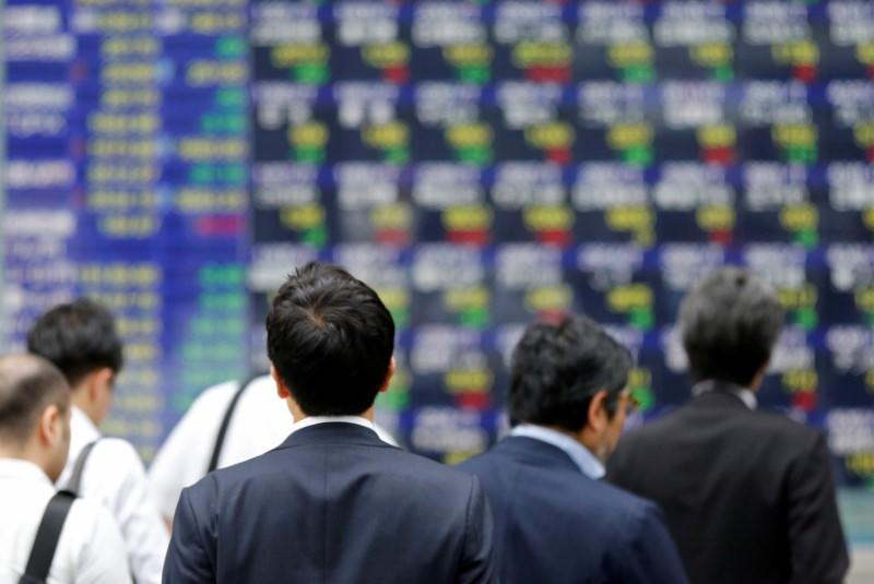 People walk past an electronic stock quotation board outside a brokerage in Tokyo