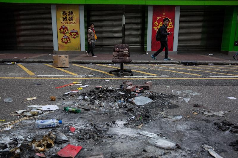 People walk past burnt debris scattered across the street following overnight clashes between protesters and police in the Mongkok area of Hong Kong on February 9, 2016 (AFP Photo/Dale de la Rey)