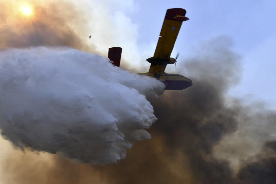 An aircraft drops water during a wildfire near Olympia town, western Greece, Thursday, Aug. 5, 2021. Wildfires rekindled outside Athens and forced more evacuations around southern Greece Thursday as weather conditions worsened and firefighters in a round-the-clock battle stopped the flames just outside the birthplace of the ancient Olympics. (Giannis Spyrounis/ilialive.gr via AP)