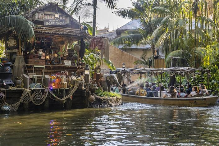 A baby elephant sprays water at a Jungle Cruise boat as they pass by Trader Sam's Gift Shop