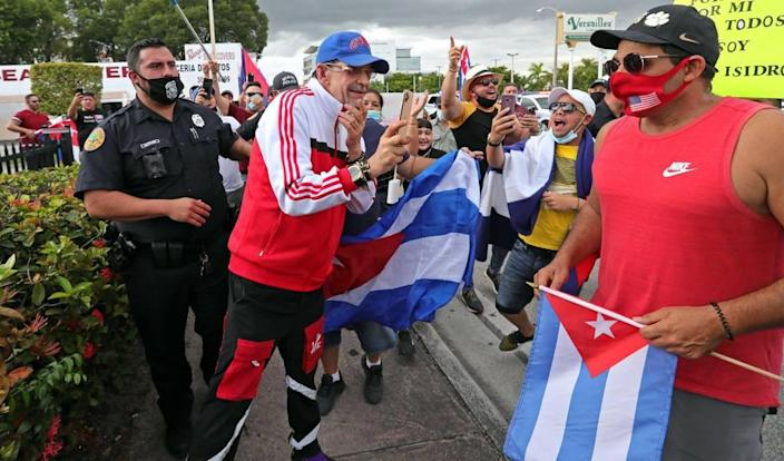 A counter protestor, wearing blue cap, is shouted down as he is escorted by Miami Police during a rally in front of Versailles Restaurant in Miami in support of Cuban artists arrested in Cuban on Saturday, November 28, 2020.