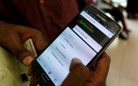 FILE PHOTO: An employee assists a customer to set-up M-Pesa money transfer servive on his handset inside a mobile phone care centre operated by Kenyan's telecom operator Safaricom; in the central business district of Kenya's capital Nairobi, May 11, 2016. REUTERS/Thomas Mukoya