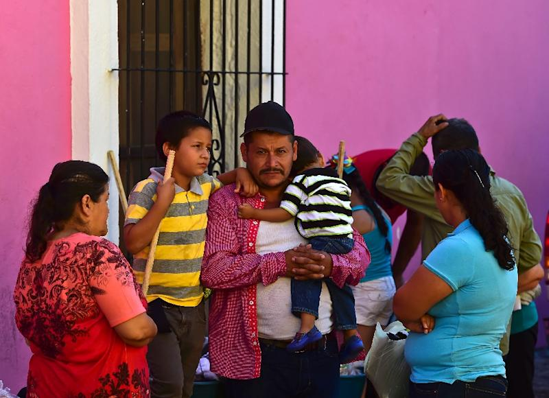 A Mexican family displaced by violence and operations against drug trafficking wait for food in front of a temporary shelter in Cosala town, Sinaloa State, on October 17, 2015 (AFP Photo/Ronaldo Schemidt)