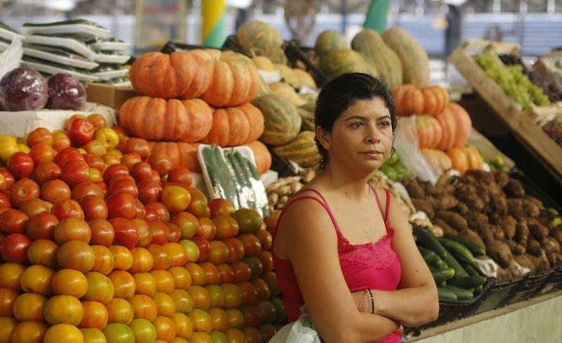 A vendor displays fruit and vegetables at her stand in the port market in the World Cup venue of Cuiaba