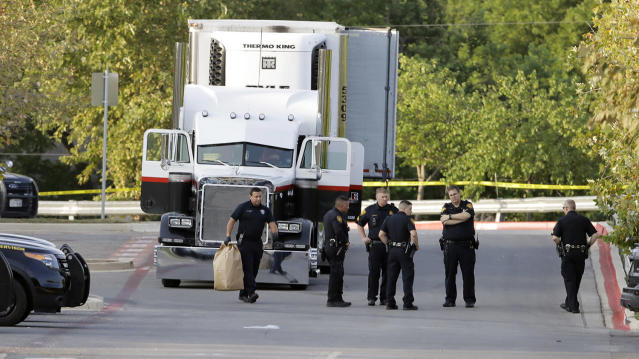 <p>San Antonio police officers investigate the scene Sunday, July 23, 2017, where eight people were found dead in a tractor-trailer loaded with at least 30 others outside a Walmart store in stifling summer heat in what police are calling a horrific human trafficking case, in San Antonio. (AP Photo/Eric Gay) </p>