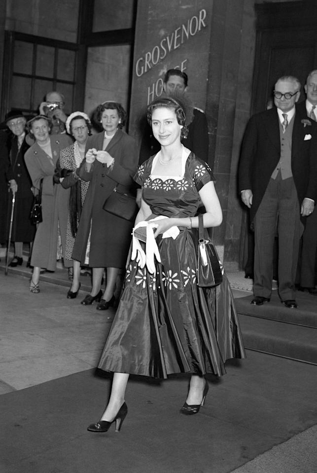 <p><b>The princess in London wearing a dress patterned with large daisy chains and a small hat trimmed with large fan shaped frills. <em>[Photo: PA]</em> </b></p>