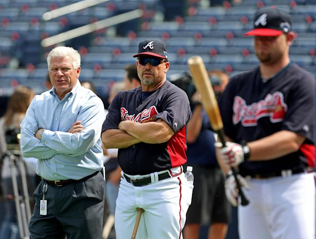 Atlanta Braves general manager Frank Wren, left, talks with manager Fredi Gonzalez as they watch batting practice Wednesday, Oct. 2, 2013, in Atlanta. The Braves are scheduled to play the Los Angeles Dodgers in Game 1 of baseball's NL division series on Thursday. (AP Photo/Atlanta Journal Constitution, Jason Getz)