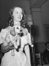 """<p>Davis held a """"Tailwaggers Party"""" in 1938, a benefit to raise money for stray dogs. In this image, she holds up a puppy that was raffled off to raise money.<br></p>"""
