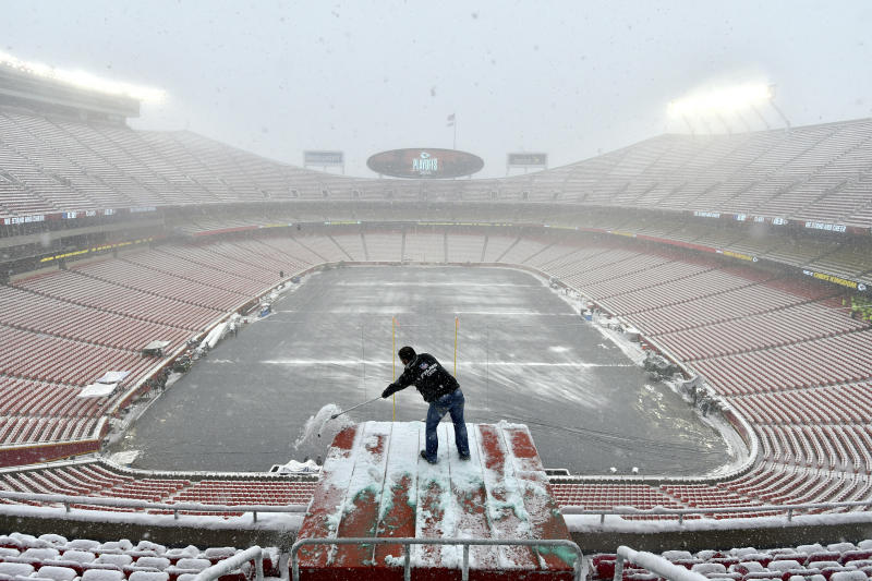 Kyle Haraugh, of NFL Films, clears snow from a camera location at Arrowhead Stadium before an NFL divisional football playoff game between the Kansas City Chiefs and the Indianapolis Colts, in Kansas City, Mo., Saturday, Jan. 12, 2019. (AP Photo/Ed Zurga)