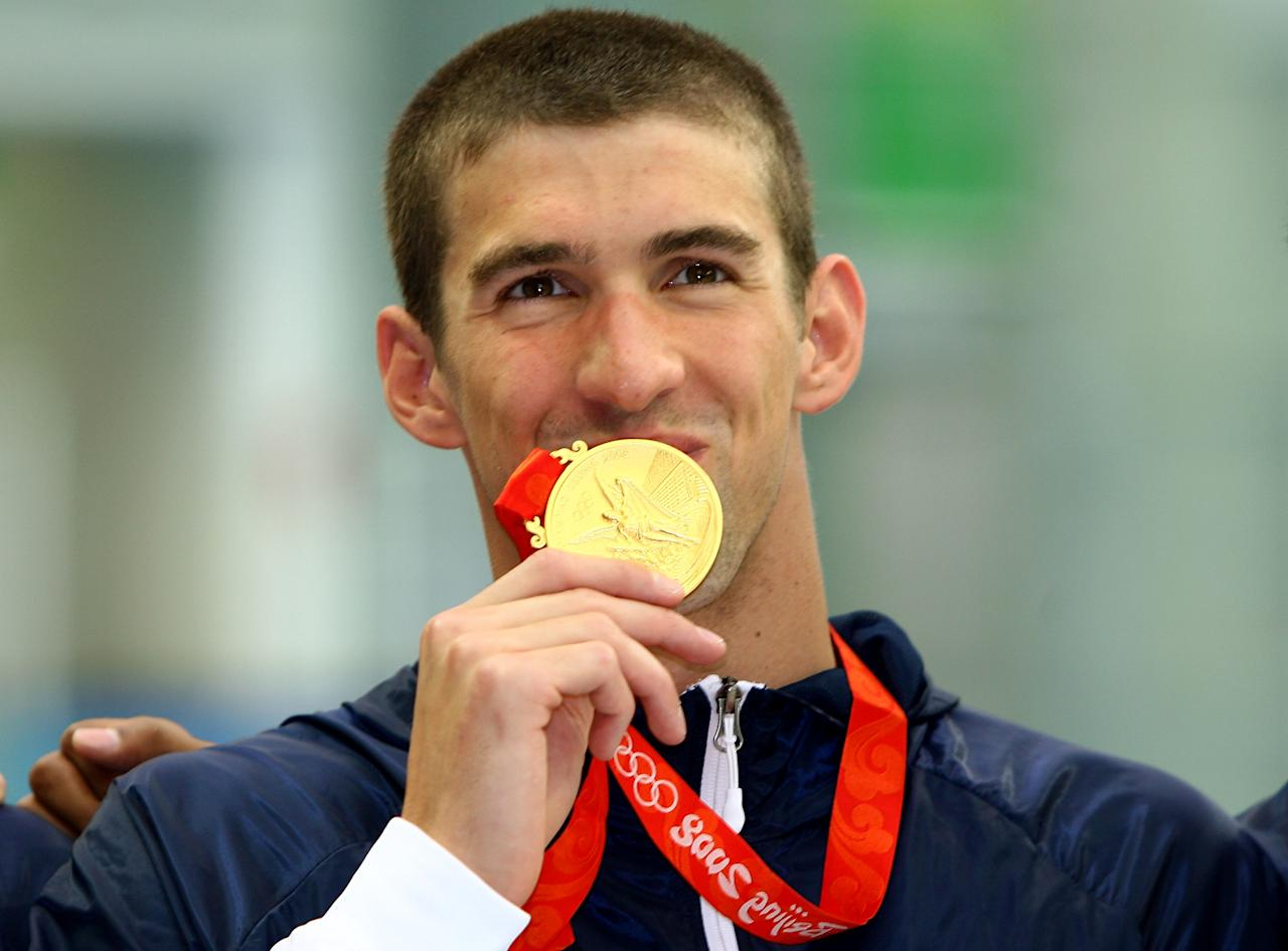 BEIJING - AUGUST 11:  Michael Phelps of the United States poses with the gold medal during the medal ceremony for the Men's 4 x 100m Freestyle Relay held at the National Aquatics Center on Day 3 of the Beijing 2008 Olympic Games on August 11, 2008 in Beijing, China.  (Photo by Adam Pretty/Getty Images)