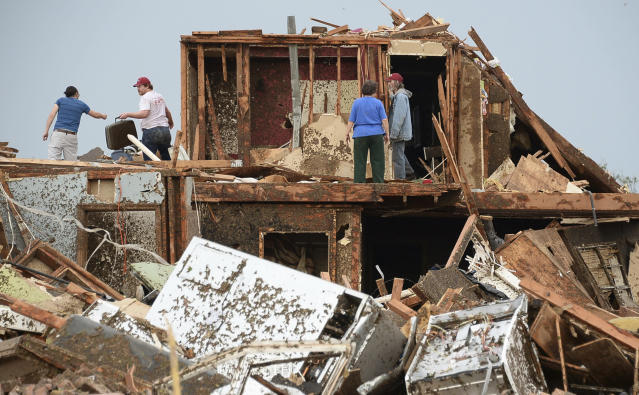 People look for belongings after a tornado struck Moore, Oklahoma, May 20, 2013. A 2-mile-wide (3-km-wide) tornado tore through the Oklahoma City suburb of Moore on Monday, killing at least 51 people while destroying entire tracts of homes, piling cars atop one another, and trapping two dozen school children beneath rubble. REUTERS/Gene Blevins (UNITED STATES - Tags: ENVIRONMENT) - RTXZUOO