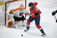 Washington Capitals right wing Anthony Mantha (39) handles the puck in front of Philadelphia Flyers goaltender Brian Elliott (37) during the first period of an NHL hockey game Tuesday, April 13, 2021, in Washington. (AP Photo/Nick Wass)