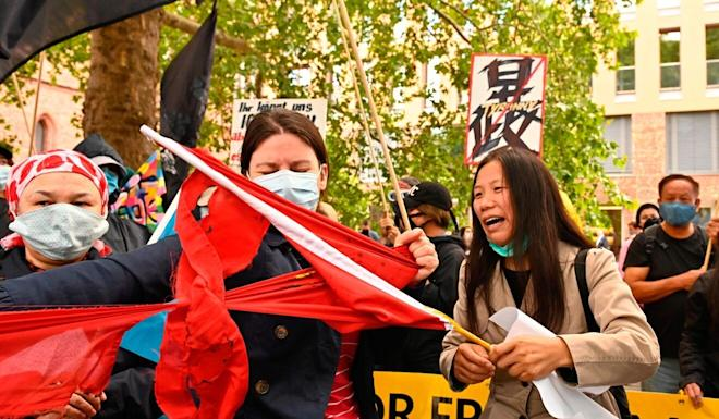 Protesters tear up a flag of China during a demonstration on Tuesday outside the Foreign Office in Berlin. Photo: AFP