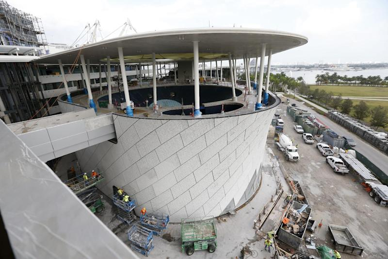 In this Thursday, Dec. 8, 2016 photo, the building housing the aquarium at the Patricia and Phillip Frost Museum of Science is shown under construction in Miami. Rising next to Miami's spiffy new bayside art museum is a $305 million science museum that, like South Florida, is focused in large part on water: its centerpiece is a 500,000-gallon aquarium that will feature sharks, tuna, mahi-mahi and even sea turtles, with other smaller tanks for corals and other sea life. The Frost Science Museum, scheduled to open this spring. (AP Photo/Wilfredo Lee)