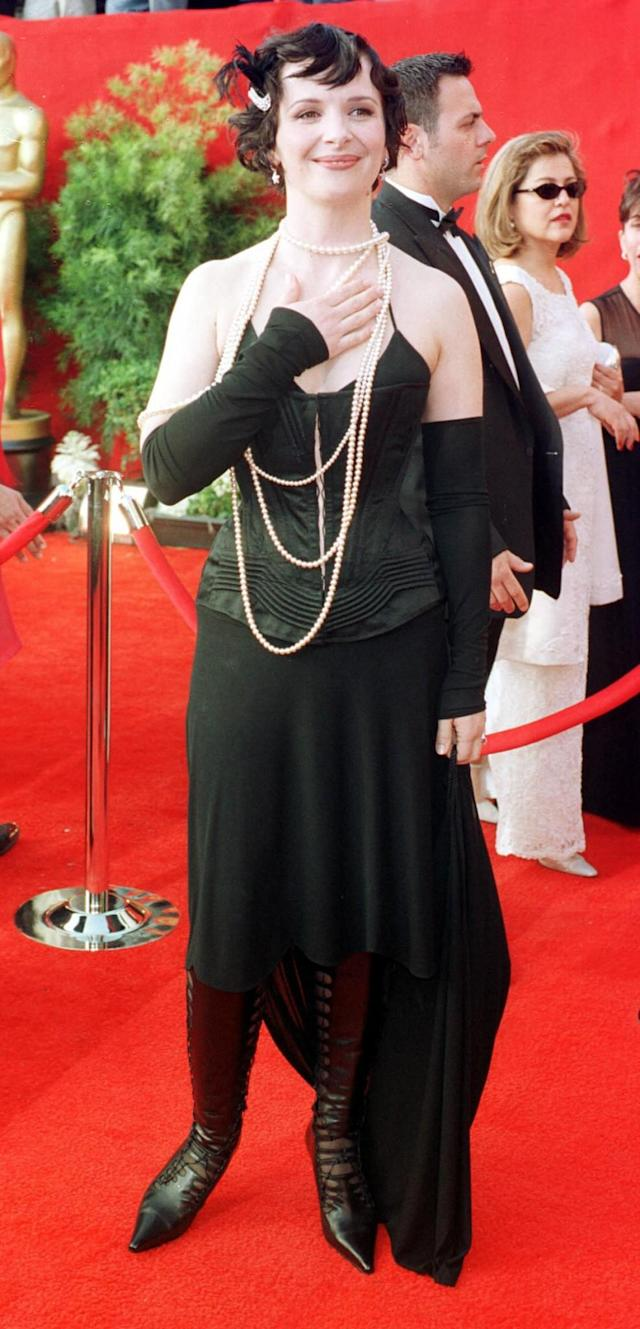 <p>Binoche went with a mixed look at the 2001 awards, pairing a flapper look above the knees with leather boots on the bottom. (Photo: PA) </p>