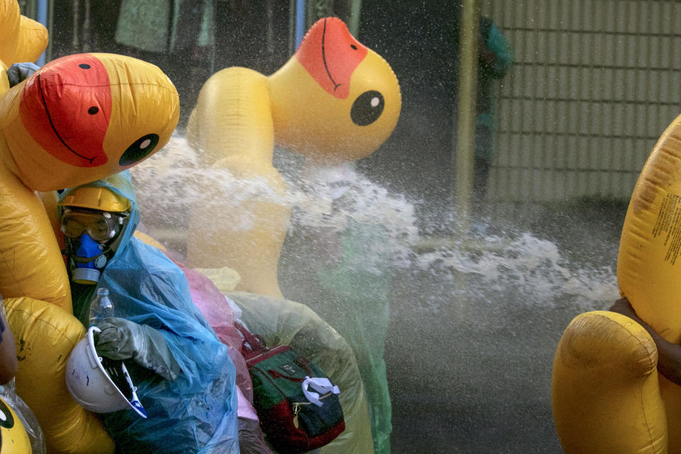 Pro-democracy protesters take cover with inflatable ducks as police fire water cannons during an anti-government rally near the Parliament in Bangkok, Tuesday, Nov. 17, 2020. Thailand's political battleground shifted to the country's Parliament Tuesday, where lawmakers are considering proposals to amend the country's constitution, one of the core demands of the student-led pro-democracy movement. (AP Photo/Wason Wanichakorn)
