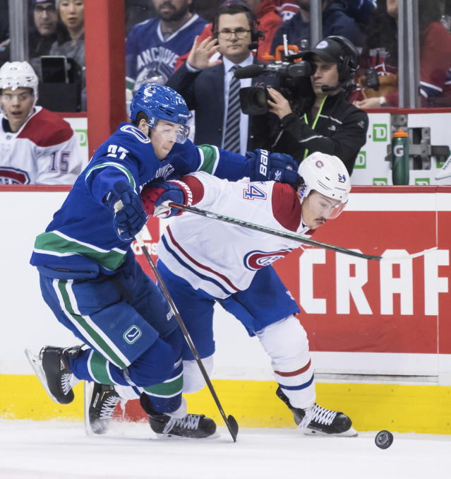 Vancouver Canucks' Ben Hutton, left, and Montreal Canadiens' Charles Hudon vie for the puck during the first period of an NHL hockey game in Vancouver, British Columbia, Saturday, Nov. 17, 2018. (Darryl Dyck/The Canadian Press via AP)
