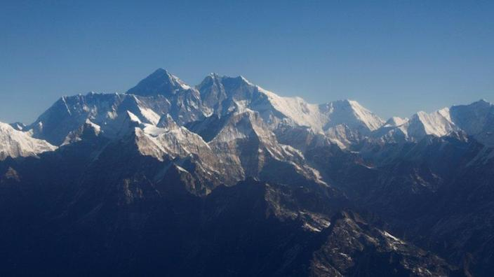 """Mount Everest, the world""""s highest peak, and other peaks of the Himalayan range are seen through an aircraft window during a mountain flight from Kathmandu, Nepal."""