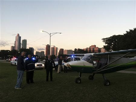 John Pedersen, pilot of a small plane that was forced to make an emergency landing, speaks to emergency personnel on Lake Shore Drive in Chicago in this handout photo taken September 22, 2013, courtesy of Chicago Sun-Times. REUTERS/Chicago Sun-Times/Ashley Rezin/Handout via Reuters