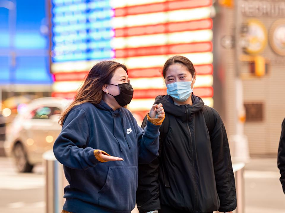 NEW YORK, NEW YORK - OCTOBER 28: People wear face masks by the U.S. Armed Forces Recruiting Station in Times Square as the city continues the re-opening efforts following restrictions imposed to slow the spread of coronavirus on October 28, 2020 in New York City. The pandemic has caused long-term repercussions throughout the tourism and entertainment industries, including short-term and permanent closures of historic and iconic venues, and costing the city and businesses billions in revenue.  (Photo by Noam Galai/Getty Images)