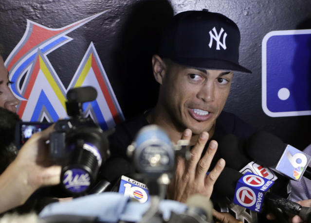 New York Yankees left fielder Giancarlo Stanton talks with the news media before a baseball game against the Miami Marlins, Tuesday, Aug. 21, 2018, in Miami. Stanton says it's weird to return to Miami, where he played his first eight major league season and will now try to help the Yankees beat the Marlins. (AP Photo/Lynne Sladky)