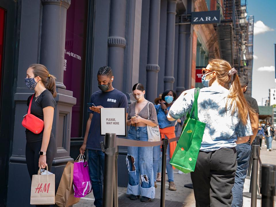 Customers wait in a line before entering a store on Broadway while wearing protective masks in the retail shopping district of the SoHo neighborhood of the Manhattan borough of New York, Friday, May 14, 2021.  (AP)