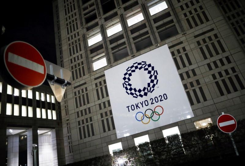 The logo of Tokyo 2020 Olympic Games is seen through signboards, in Tokyo