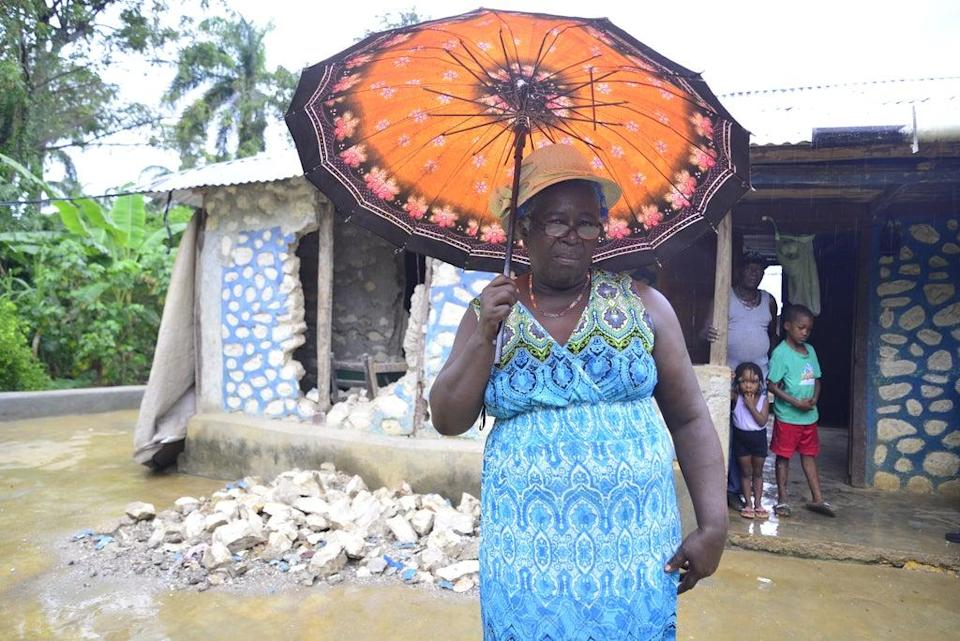 Estabelle stands in front of what is left of her home (ActionAid )