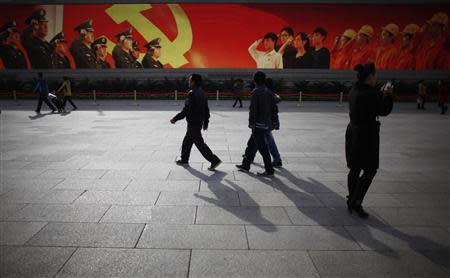 People walk in front of a screen showing propaganda displays near the Great Hall of the People at Beijing's Tiananmen Square, in this file picture taken November 7, 2012. REUTERS/Carlos Barria/Files