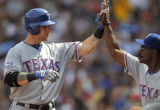 Texas Rangers' Josh Hamilton, left, is welcomed to the dugout by' manager Ron Washington after hitting a two-run home run off a pitch by Boston Red Sox's Josh Beckett in the fifth inning of a baseball game at Fenway Park in Boston, Wednesday, Aug. 8, 2012. (AP Photo/Steven Senne)