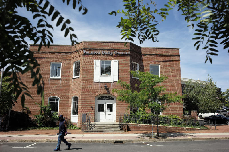 In this Monday, Aug. 5, 2019 photo a passer-by walks near an entrance to the Taunton Daily Gazette newspaper's offices, in Taunton, Mass. The newspaper is published by GateHouse Media New England, a division of GateHouse Media Inc. On Monday, GateHouse Media, a chain backed by an investment firm, announced that it is buying USA Today owner Gannett Co. (AP Photo/Steven Senne)