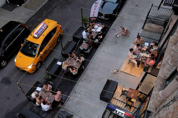 PHOTO: People eat outside of LENA Winebar as restaurants are permitted to offer al fresco dining as part of phase 2 reopening during the COVID-19 outbreak in the Lower East Side of Manhattan in New York City, June 27, 2020. (Andrew Kelly/Reuters)