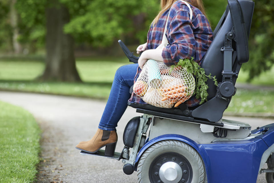 A woman in a disability scooter with her shopping. Source: Getty Images