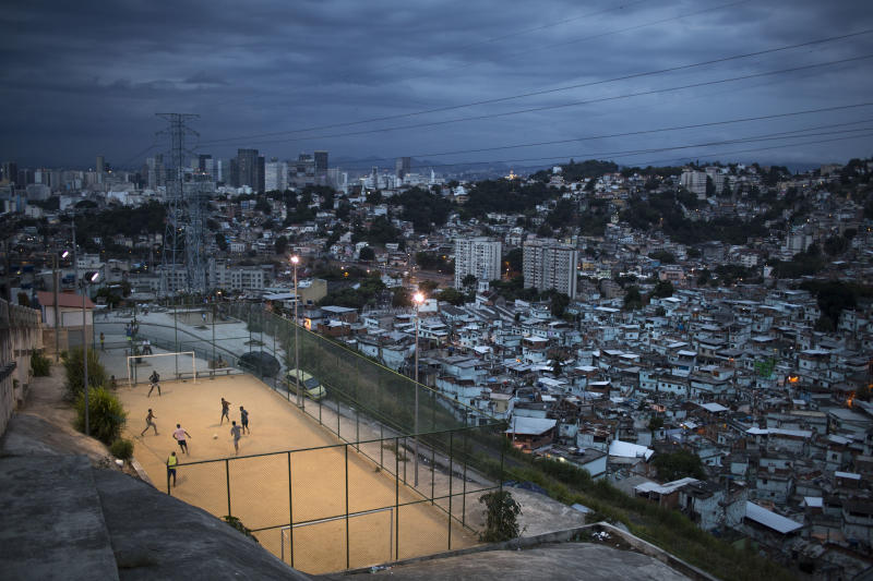 """In this March 7, 2014 photo, boys play soccer in the Sao Carlos slum after sunset in Rio de Janeiro, Brazil. The first thing Brazilian kids often do before pick-up games is play """"rock, scissors, paper"""" to decide who will be goalkeeper. With so many outstanding strikers and midfielders in Brazilian history, few chose goalkeepers as their childhood idols. (AP Photo/Felipe Dana)"""