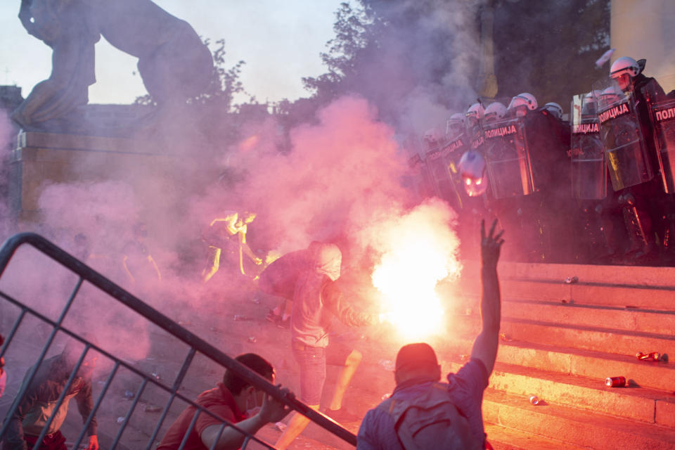 Protesters clash with riot police on the steps of the Serbian parliament in Belgrade, Serbia, Wednesday, July 8, 2020. Police have fired tear gas at protesters in Serbia's capital during the second day of demonstrations against the president's handling of the country's coronavirus outbreak. President Aleksandar Vucic backtracked on his plans to reinstate a coronavirus lockdown in Belgrade this week, but it didn't stop people from firing flares and throwing stones while trying to storm the downtown parliament building. (AP Photo/Marko Drobnjakovic)